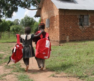 Two children walk side by side with their new Kinder Kits